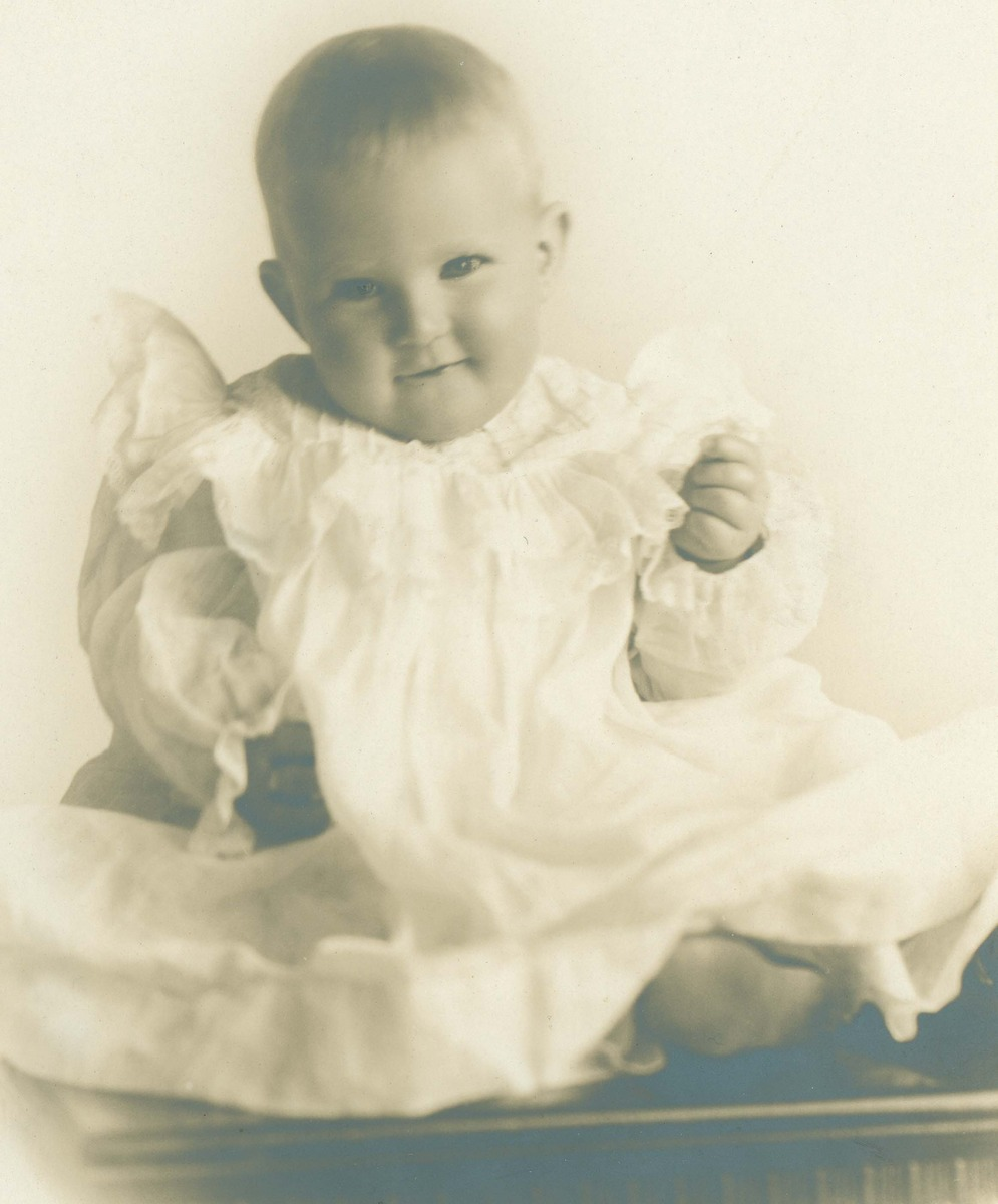 Seated baby in ruffled christening gown
