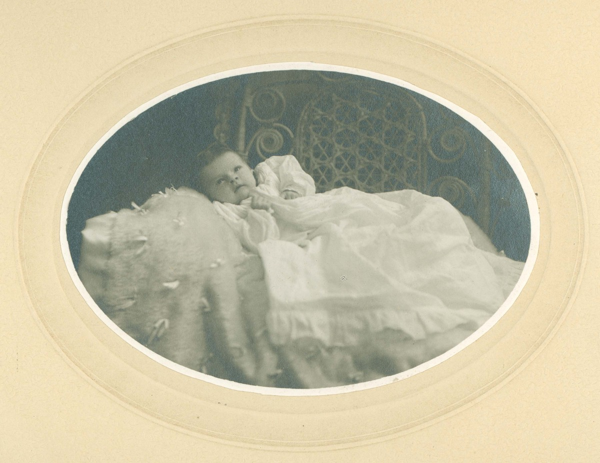 Baby in christening gown, on fluffy blanket laid on ornate cane chair