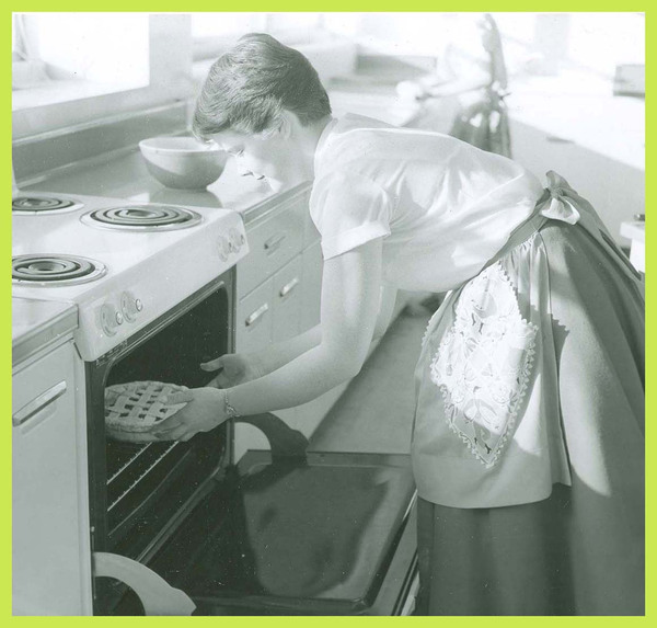A student places a pie in the oven.