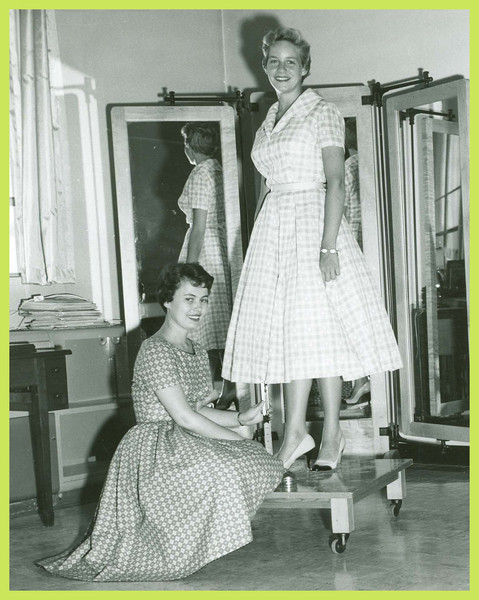 Two women pose while measuring a hemline.