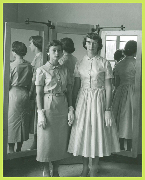 Two women pose in front of a mirror in the Women's Center.