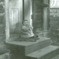 Baby Ruth Asbridge sitting on steps at Lazy X Ranch near Roundup, MT