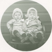 Toddler and baby sitting in chair with knitted hats and identical outfits