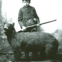84-274,boy with rifle posed with stuffed bear.jpg