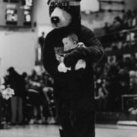 Monte poses with a young fan at a basketball game.